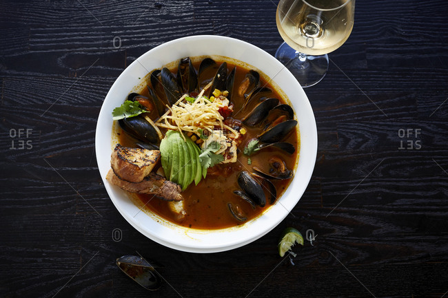 Mussels in broth with avocado, bread and wine