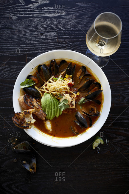 Mussels in broth with avocado, bread and wine from above