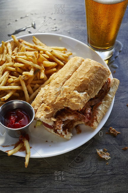 Fried chicken sandwich on a white plate with French fries