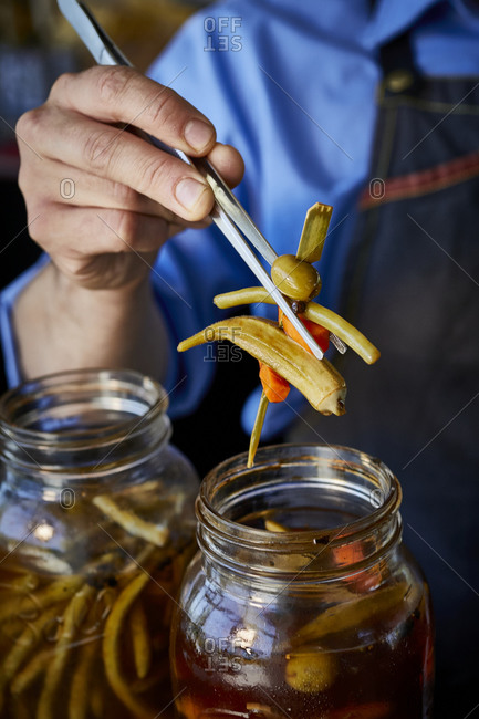 Bartender preparing pickled vegetables on a bar top for bloody Mary