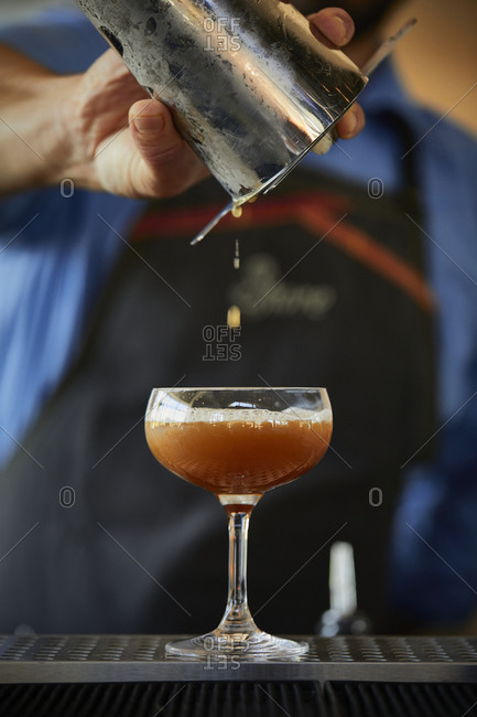Bartender pouring a cocktail at the bar