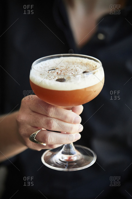 Hand holding a cocktail drink
