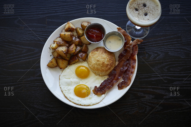 Bacon, eggs, potatoes and a biscuit for brunch with cocktail