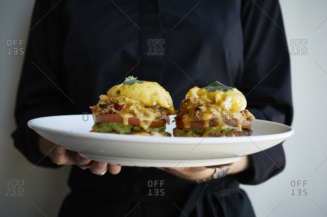 Server holding brunch sandwich with poached eggs