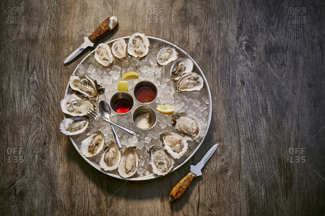 Overhead view of an oyster appetizer on a rustic wooden surface