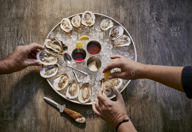 Overhead view of people eating an oyster appetizer on a rustic wooden surface