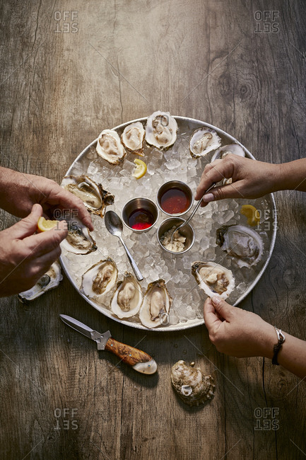 Two people eating an oyster appetizer on a rustic wooden surface