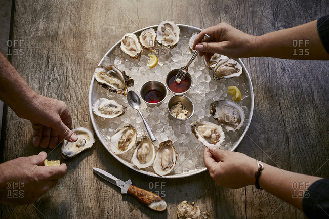 Two people enjoying an oyster appetizer on a rustic wooden surface