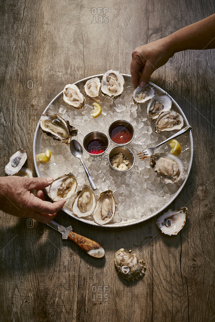 Two people eating an oyster appetizer on a rustic wooden surface from above