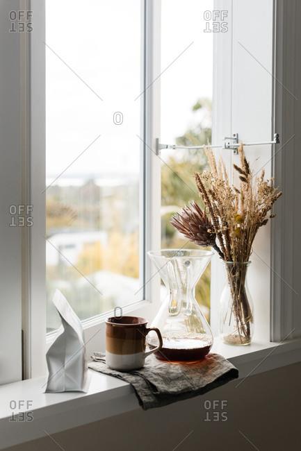 Coffee carafe by mug on windowsill