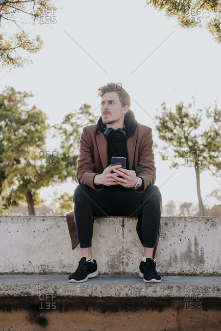 Young blonde boy sitting on a concrete bench holding his mobile and wearing a brown trench coat and headphones looking into the distance during the sunset