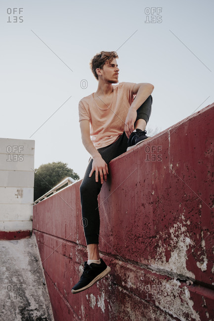 Young skinny boy resting in a concrete red wall during the sunset looking into the distance