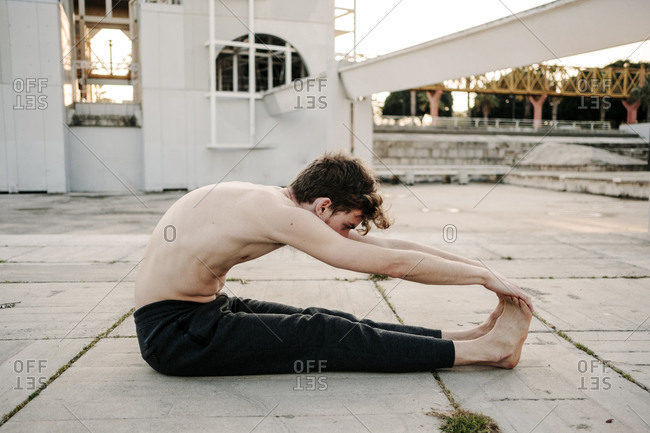 Young boy practicing yoga stretches sitting on concrete floor during sunset