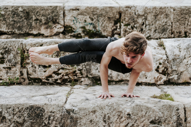 Young boy practicing yoga position on his hands in the city on stone stairs