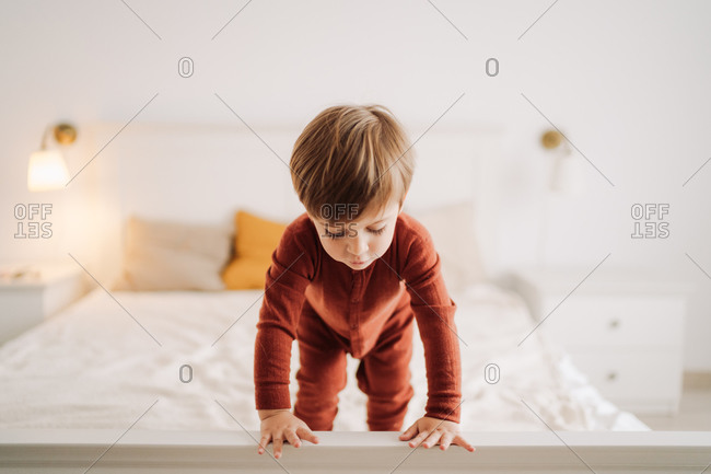 Kid looking over edge of bed