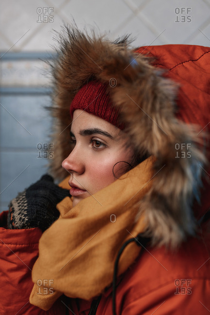 Close up of a young caucasian woman wearing an orange coat