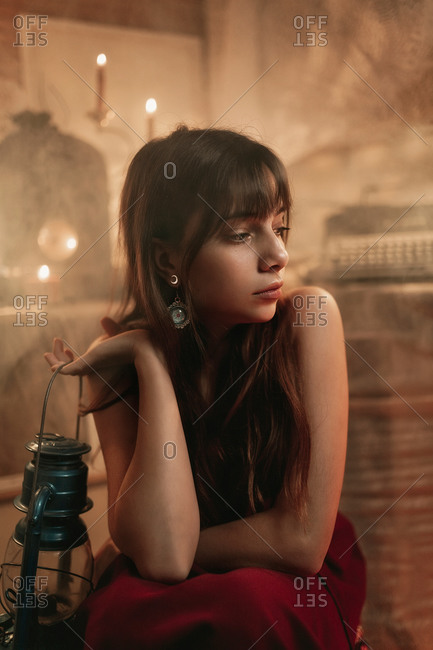 Portrait of a young woman in her twenties wearing a long red dress sitting and holding an old blue hand lamp inside her studio with candles and fog in the air.