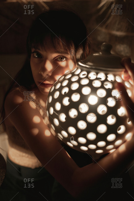 Portrait of a young woman in her twenties holding a perforated round ceramic lamp with a bulb light.