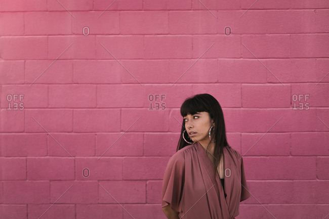 Portrait of a young eccentric woman with strange big earrings and piercings, wearing a pink dress infront of a pink brick wall