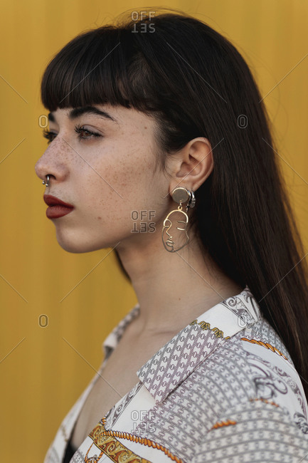Close up portrait of a young eccentric woman with earrings in the shape of a face with closed eyes looking away.