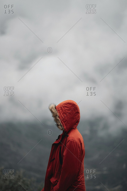 Anonymous explorer with an orange coat and the hoodie on, standing alone on the peak of a mountain in Grazalema, Spain.