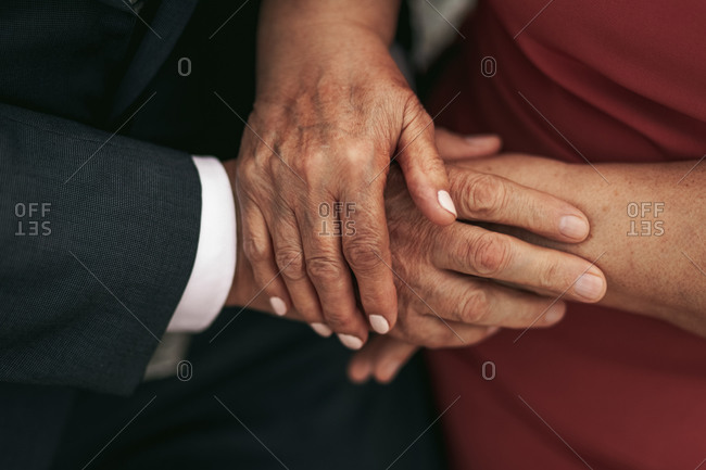 Close up of elderly couple holding hands with love and kindness