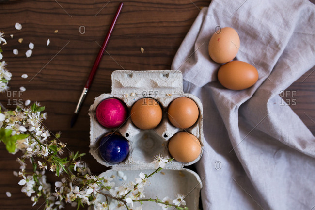 Dyed Easter eggs on table with branch of cherry blossom