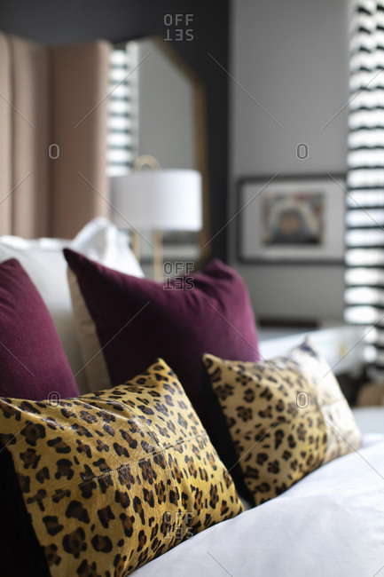 Animal print and mauve pillows on a bed