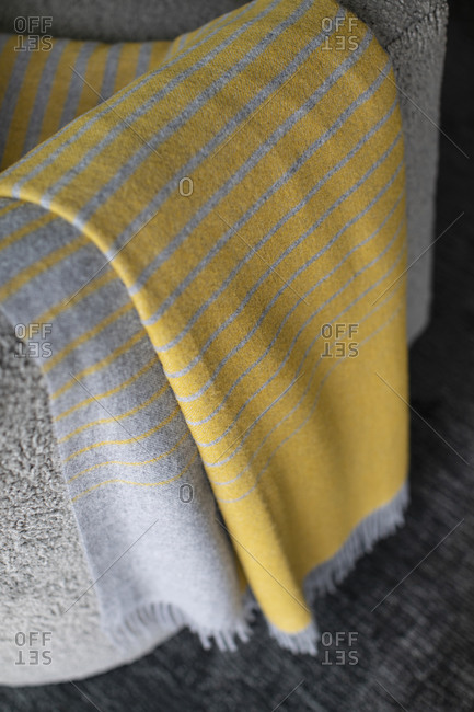 Striped yellow blanket draped over sofa arm