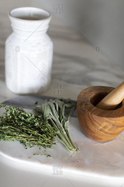 Herbs and a wooden mortar and pestle on marble surface