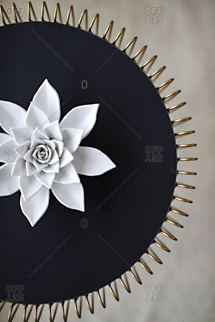 Decorative artwork with large white flower and gold edges