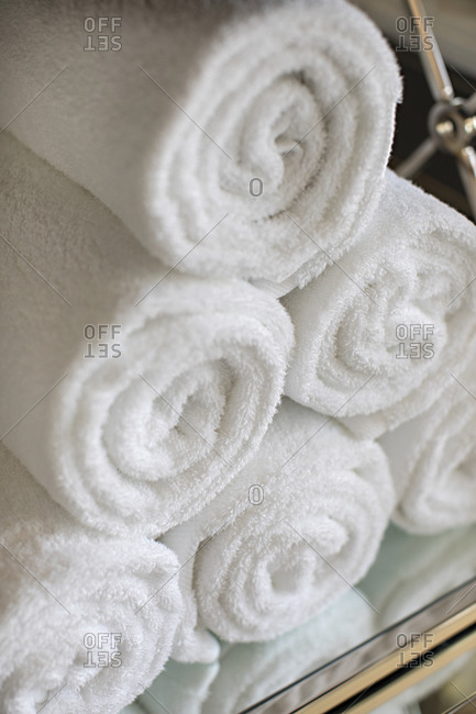 White rolled towels on a mirrored shelf