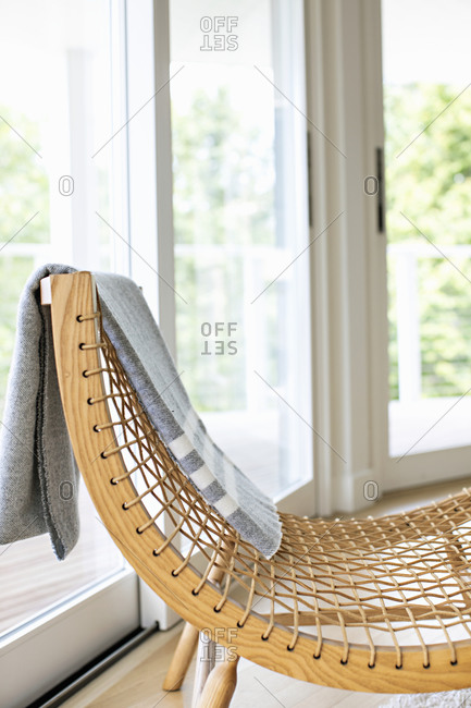 Gray blanket draped over wooden string chair