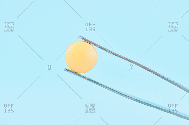 Yellow  pills and tweezer for medical concept