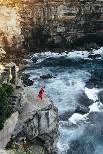 Woman dancer wearing a red dress overlooking the ocean