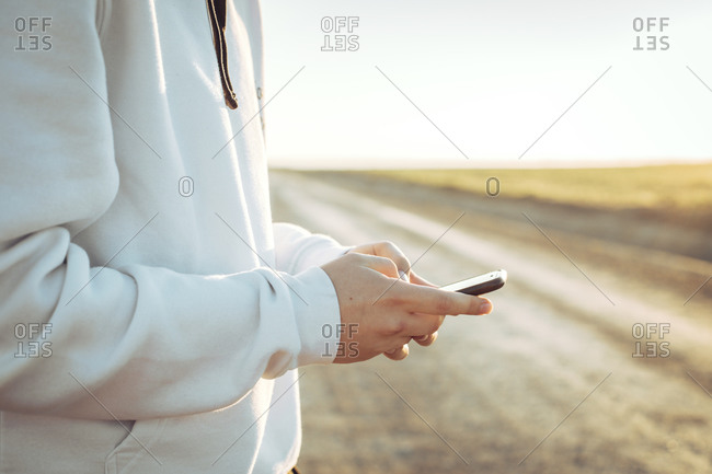 Close-up of the hands of a young boy typing on his mobile phone during sunset