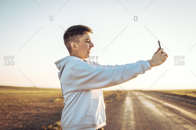 Young boy taking a selfie with his mobile while smiling in the field during sunset