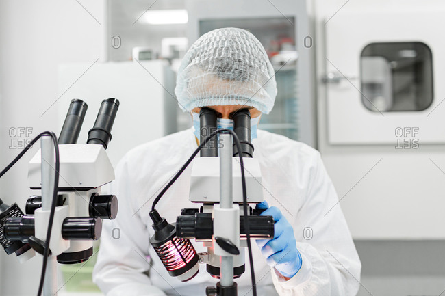 A scientist works with a microscope in the laboratory. Conducts research of biomaterial samples.