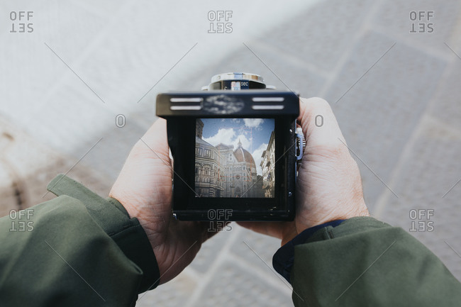 Man holds old film camera with both hands, with a photo of the Santa Maria del Fiore Cathedral and nearly empty Piazza del Duomo