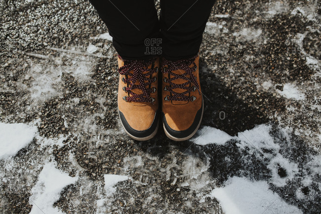 Woman's feet while wearing snow boots on black ice and snow.