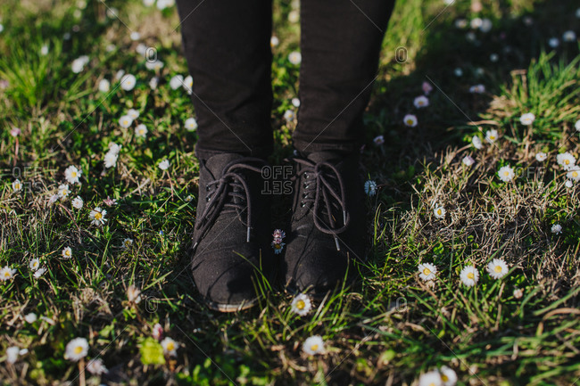 Woman wearing black pants and black shoes stands on a field of wild flowers in Tuscany