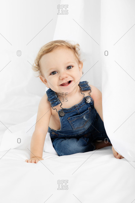 Cute happy baby hiding under white sheet on bed