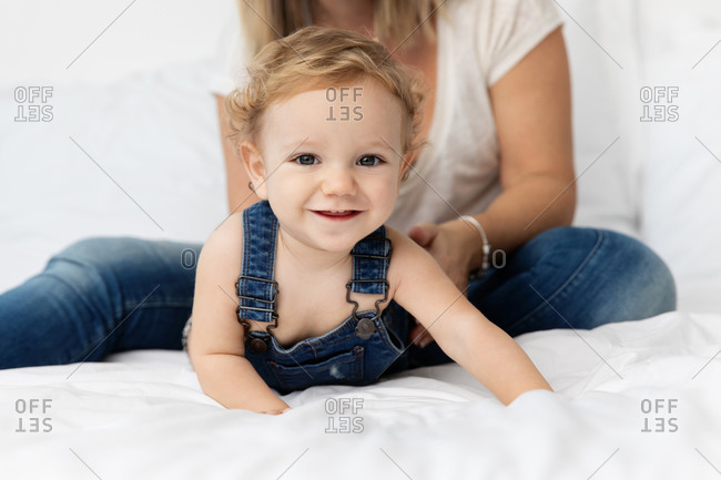 Smiling baby playing with mother on white bed