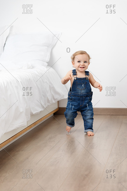 Happy baby making first steps in bedroom