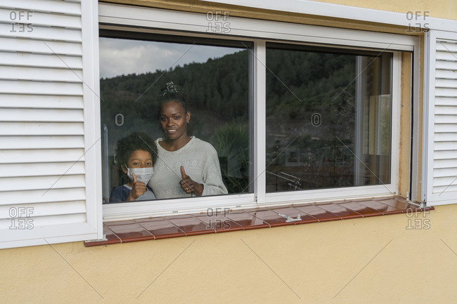 Mother hugs her African-American son affected by coronavirus in a medical mask as they look out the window smiling in victory
