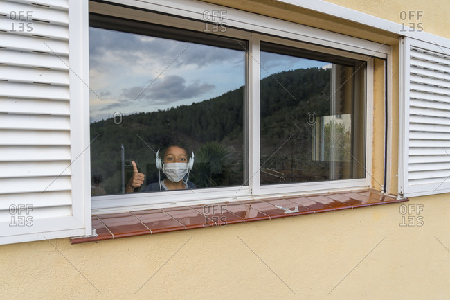 African-American kid affected by coronavirus looking through the window and wearing mask protection while making the victory sign