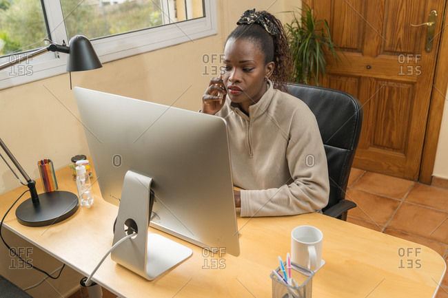 Black woman teleworking from her living room because of coronavirus confinement