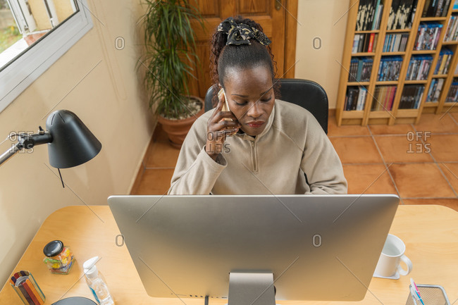 Beautiful black woman freelancer teleworking from her living room because of coronavirus confinement