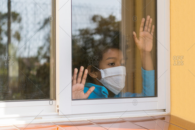 Sad lonely boy isolated at home in protective sterile medical mask on her face looking through the window affected by coronavirus