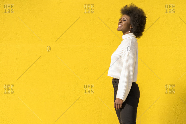 Young cool woman with Afro hair casual clothes laughing and looking away with yellow wall on background
